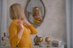 Девушка в желтом платье смотря в зеркале и усмехаться стоковое изображение