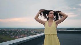 Девушка в желтом платье танцующ и представляющ на крыше На заднем плане голубое небо и крыши домов сток-видео