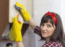 Девушка в желтых перчатках моет шкафчик в кухне, приборе конца-вверх стоковое изображение