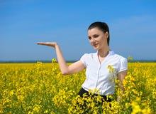 Девушка в желтом поле цветка Покажите ладонь Держите в ладони что-то и усмехайтесь Красивый ландшафт весны, яркий солнечный день, Стоковое Изображение RF