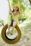 Девушка в желтом платье на качании автошины Стоковое фото RF