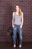 Девушка в джинсах, рубашка стоя около стены и обнимая тросточку Corso собаки Стоковое Фото