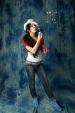 Девушка в джинсах с воздушными пузырями мыла на голубой предпосылке Стоковое Изображение