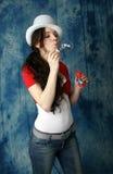 Девушка в джинсах с воздушными пузырями мыла на голубой предпосылке Стоковая Фотография RF