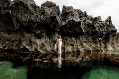 Девушка в заводи моря около скалы стоковые фото