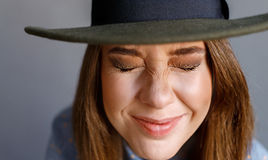 Девушка в закрытых глазах шляпы смеясь над Стоковые Фото