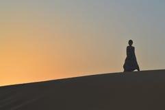 Девушка в заходящем солнце в пустыне Стоковые Фото