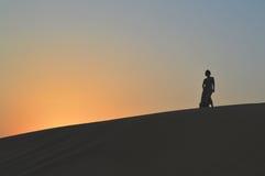 Девушка в заходящем солнце в пустыне Стоковые Изображения RF