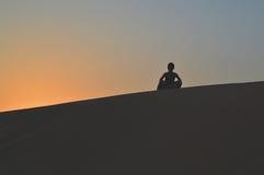 Девушка в заходящем солнце в пустыне Стоковое фото RF
