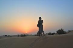 Девушка в заходящем солнце в пустыне Стоковые Фотографии RF