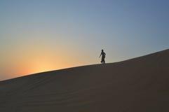 Девушка в заходящем солнце в пустыне Стоковая Фотография