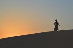 Девушка в заходящем солнце в пустыне Стоковое Фото