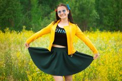 Девушка в зеленой юбке на луге цветка стоковые фотографии rf