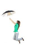 Девушка в зеленой рубашке и серых джинсах задыхается с скакать зонтика Стоковое фото RF