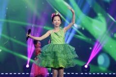 Девушка в зеленом цвете поет песню и танцует Стоковые Фотографии RF