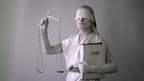 Девушка в каменном костюме статуи Femida богиня правосудия на белой предпосылке в одной руке держа масштабы сток-видео
