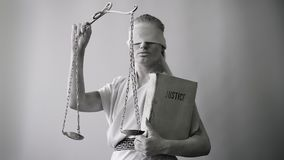 Девушка в каменном костюме статуи Femida богиня правосудия на белой предпосылке в одной руке держа масштабы акции видеоматериалы