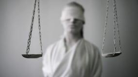 Девушка в каменном костюме статуи Femida богиня правосудия на белой предпосылке в одной руке держа масштабы видеоматериал