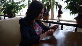 Девушка в кафе смотря телефон акции видеоматериалы