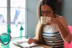 Девушка в кафе для чашки кофе с тетрадью Стоковые Фотографии RF