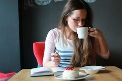 Девушка в кафе для чашки кофе с тетрадью Стоковые Изображения