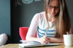 Девушка в кафе для чашки кофе с тетрадью Стоковое Изображение