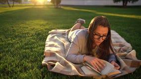 Девушка в книге чтения стекел лежа вниз на одеяле в парке на заходе солнца видеоматериал