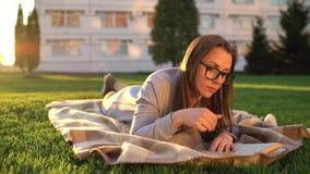 Девушка в книге чтения стекел лежа вниз на одеяле в парке на заходе солнца акции видеоматериалы