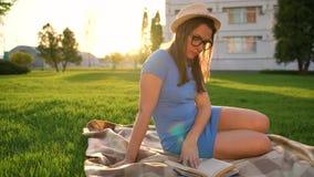 Девушка в книге чтения стекел сидя на одеяле в парке на заходе солнца сток-видео