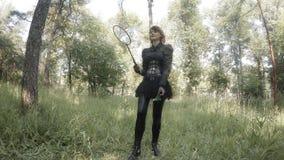 Девушка в кожаном костюме играет бадминтон на траве видеоматериал