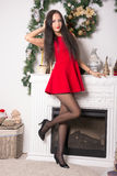 Девушка в коротком красном платье на украшениях рождества предпосылки Стоковая Фотография