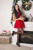 Девушка в коротком красном платье с подарком в руках стоковое изображение