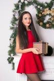 Девушка в коротком красном платье с подарком в руке на огне предпосылки стоковое фото