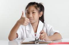 Девушка в костюме доктора работая на таблице и большом пальце руки вверх Стоковое Изображение