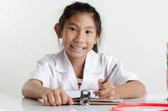 Девушка в костюме доктора работая на таблице Стоковые Изображения