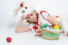 Девушка в костюме кролика с корзиной пасхальных яя Стоковые Фотографии RF