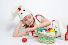 Девушка в костюме кролика с корзиной пасхальных яя Стоковые Изображения