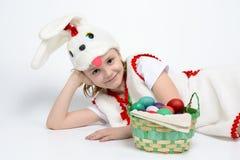 Девушка в костюме кролика с корзиной пасхальных яя Стоковые Изображения RF