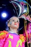 Девушка в костюме клоуна держа воздушный шар звезды форменный Стоковая Фотография