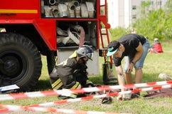Девушка в костюме пожарного подготавливая преодолевать препятствие c стоковое изображение rf