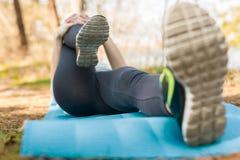 Девушка в костюме спорта, outdoors, замешивая ее ноги лежа на голубом стоковое изображение