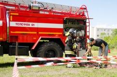 Девушка в костюме ` s пожарного против пожарной машины подготавливая к overc стоковая фотография rf
