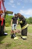 девушка в костюме ` s пожарного против пожарной машины подготавливая преодолевать полосу препятствий стоковое изображение