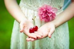 Девушка в красивом платье держит ягоды зрелых сладостных вишен Стоковые Изображения