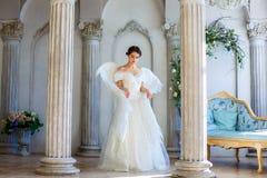 Девушка в красивом платье и белых крылах ангела воодушевляет Стоковое фото RF