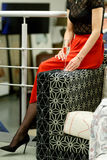 Девушка в красной и черной на кресле с стеклом стороны не видима Стоковые Фотографии RF
