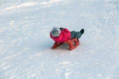 Девушка в красной куртке едет скольжение снега стоковое фото