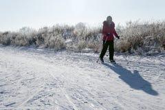 Девушка в красной куртке и черных брюках на лыжах в свете утра Предпосылка Snowy со следами, тень от женщины и copyspace стоковая фотография
