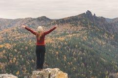 Девушка в красной куртке протягивая ее оружия на горе, взгляд гор и лес осени к пасмурный день Стоковые Изображения RF