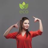 Девушка в красной рубашке, серой предпосылке Радостная молодая женщина брюнет моды Показывать на логотипе eco стоковое изображение rf